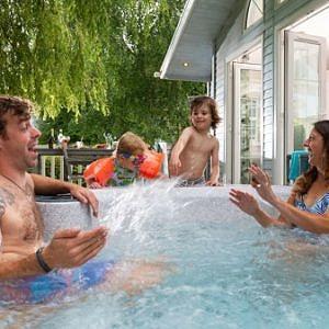 Family splashing mum in hot tub
