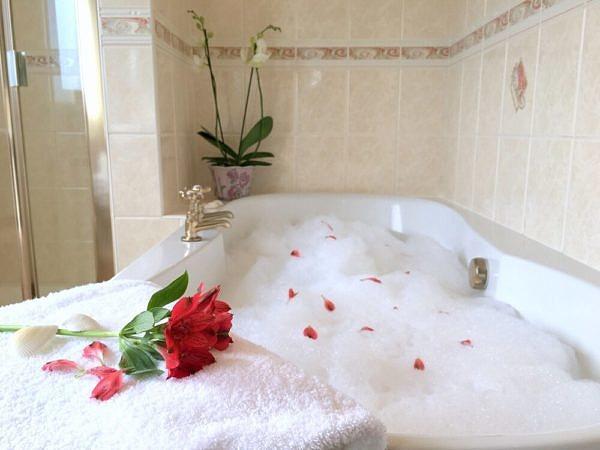 Bathtub with bubble bath foam and a flower