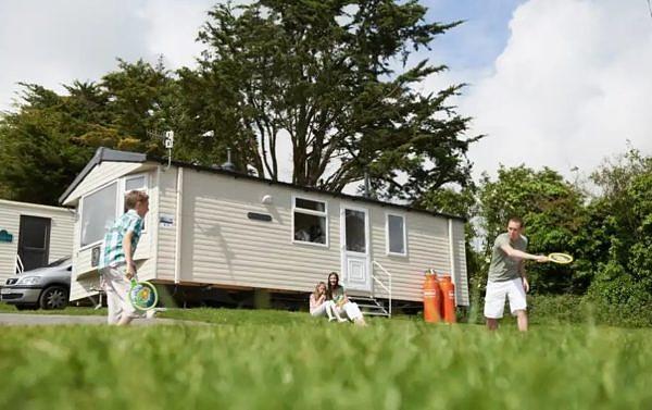 Family playing badminton outside thorpe park's caravan