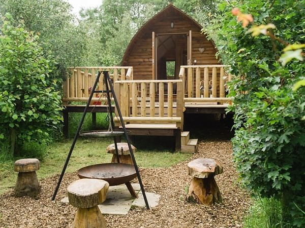 Wooden barrel cabin with veranda and bonfire place outside